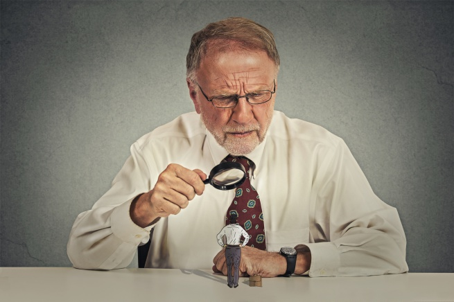 Curious corporate senior businessman skeptically meeting looking at small employee worker through magnifying glass isolated office grey wall background. Human face expression, attitude, perception